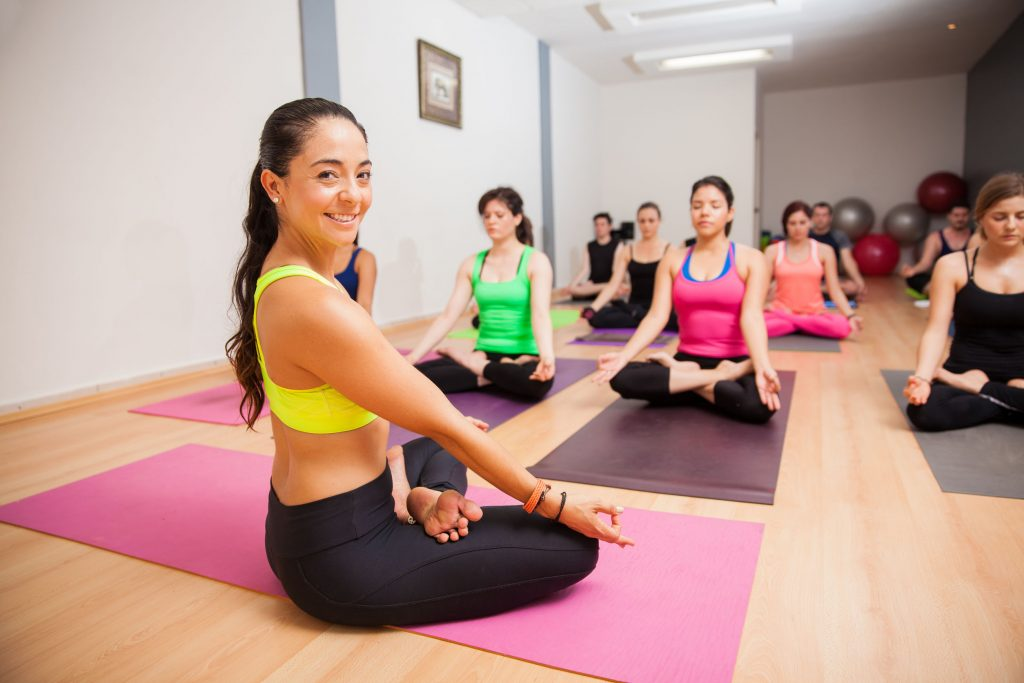 Portrait of a beautiful young yoga instructor smiling during one of her classes